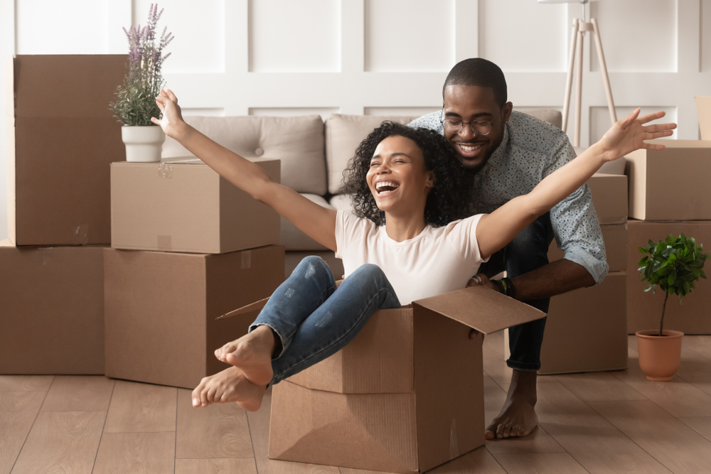 Happy Couple Unpacks Boxes in their First-Time Home Purchase