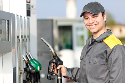 Smiling Employee Holds Pump At Gas Station