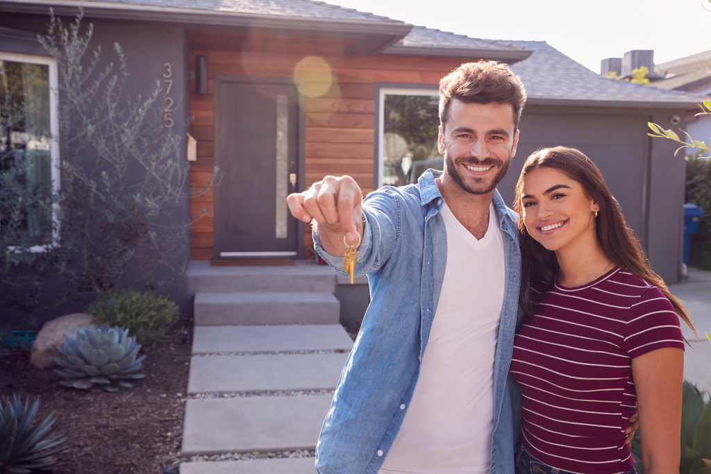 Portrait Of Homeowners Standing Outdoors In Front Of House Holding Keys