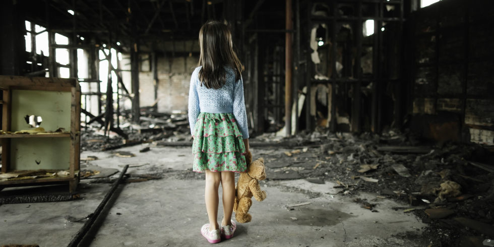 Girl Looks at House after Fire While Holding Teddy Bear
