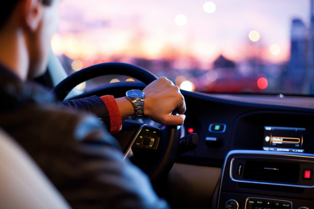 View of a Man with Great Rates from Ovation Driving a Car Towards a Sunset